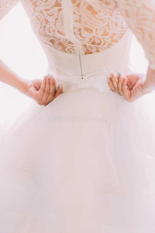 Vit bröllopsklänning för elegant stilfull tappning med prydnader och pilbågar på bruds tillbaka närbild royaltyfri fotografi