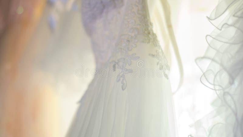 Vit bröllopsklänning med lace, sett från nära håll, i naturligt ljus arkivfoto