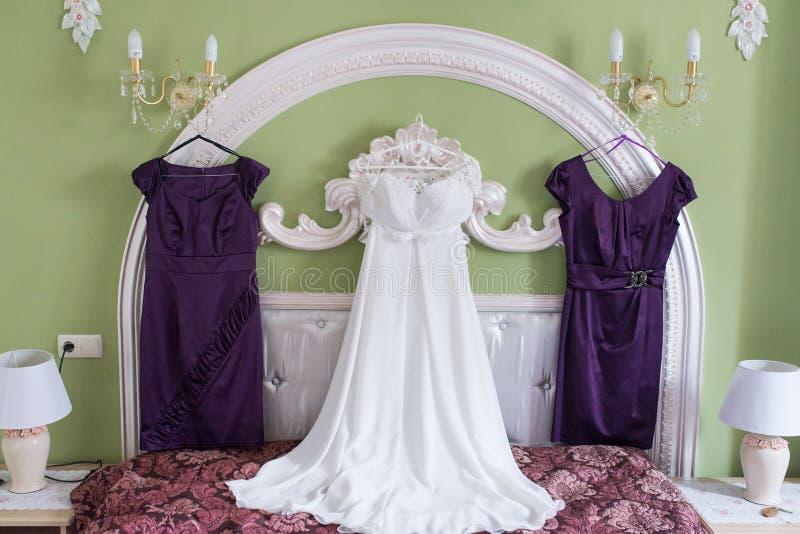 Vit bröllopsklänning och två lila bridesmaid'sklänningar på en hängare på väggen Morgon av bruden avgifter fotografering för bildbyråer