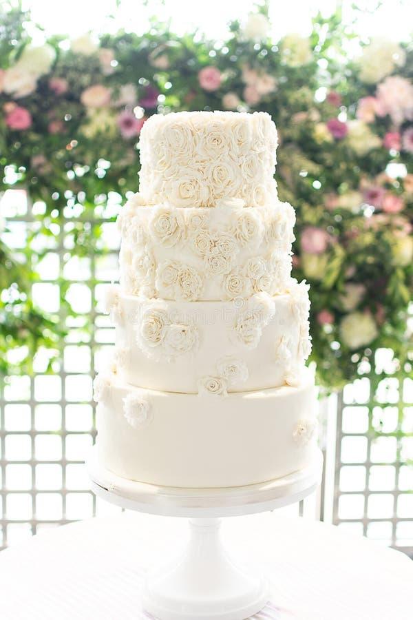 Vit bröllopstårta för 4 rad med Rosette Embellishments And Floral Background royaltyfria bilder