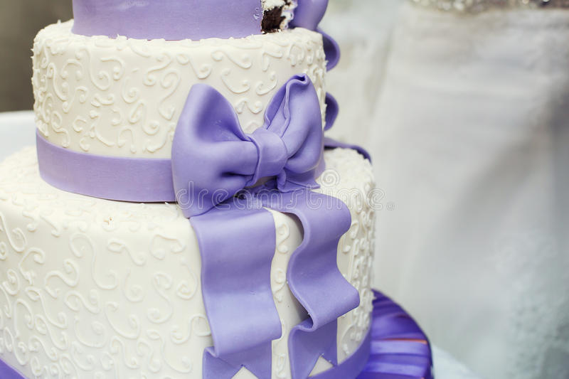 Vit bröllopstårta- och violetpilbåge royaltyfria bilder