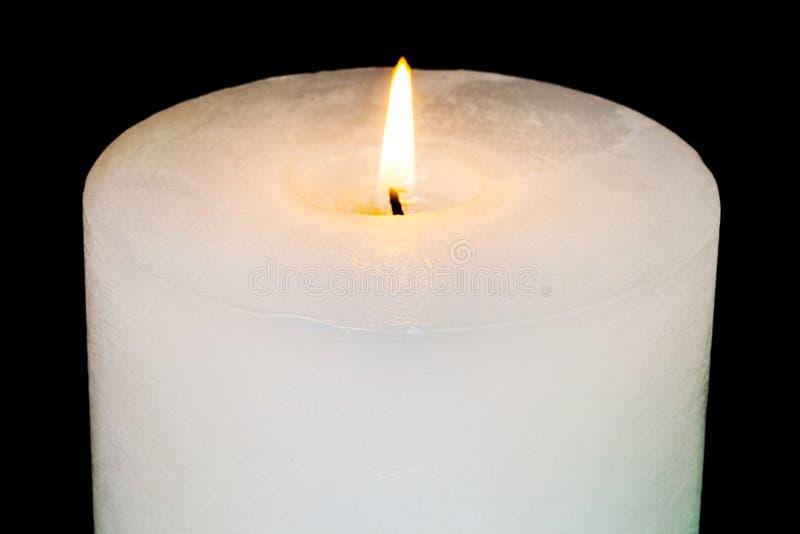 Vit brinnande stearinljus på svart slut upp royaltyfri fotografi