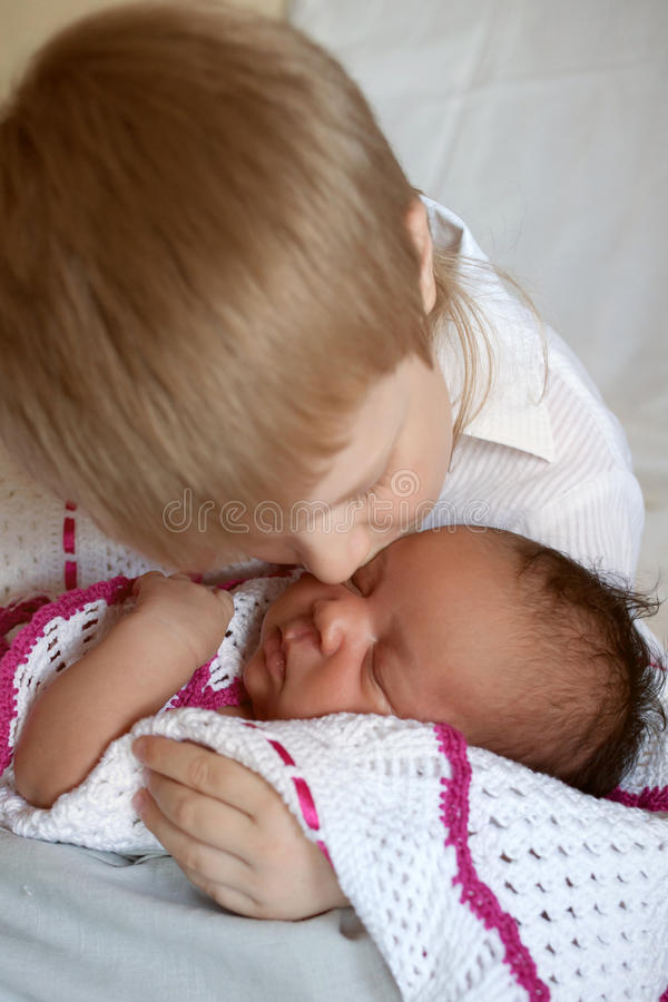 Vit broder som kramar den svarta nyfödda systern arkivfoton