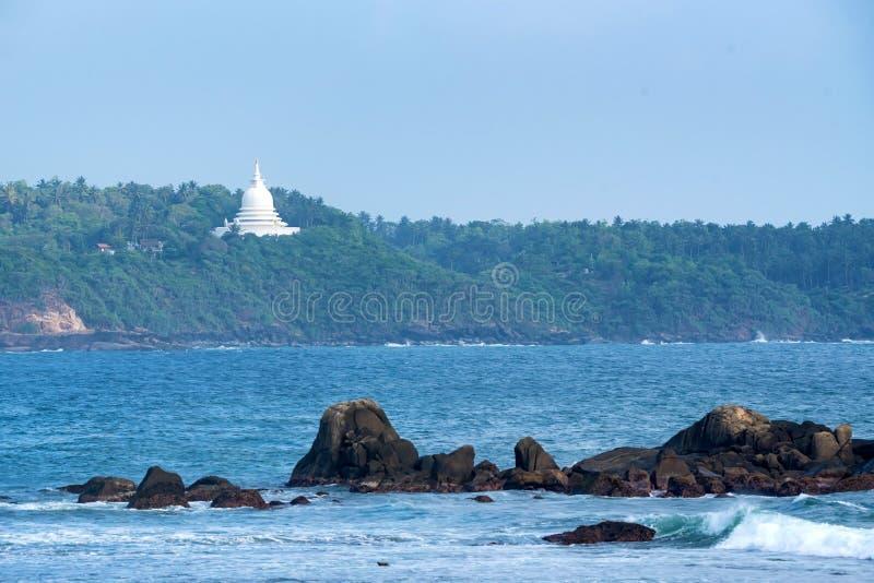 Vit buddistisk stupa på havskust i Sri Lanka fotografering för bildbyråer
