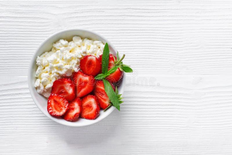 Vit bunke med nya r?da mogna jordgubbar och naturlig keso arkivfoton