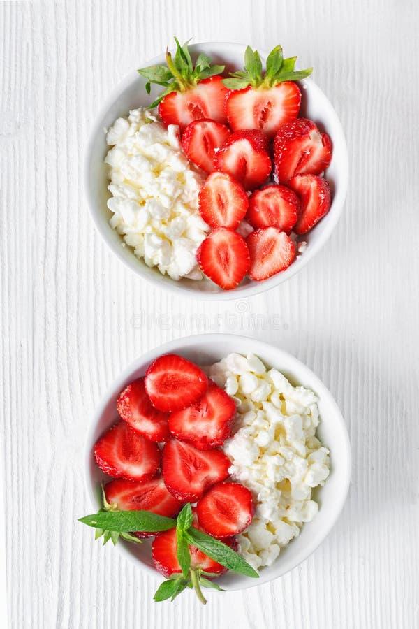 Vit bunke med nya r?da mogna jordgubbar och naturlig keso royaltyfri fotografi