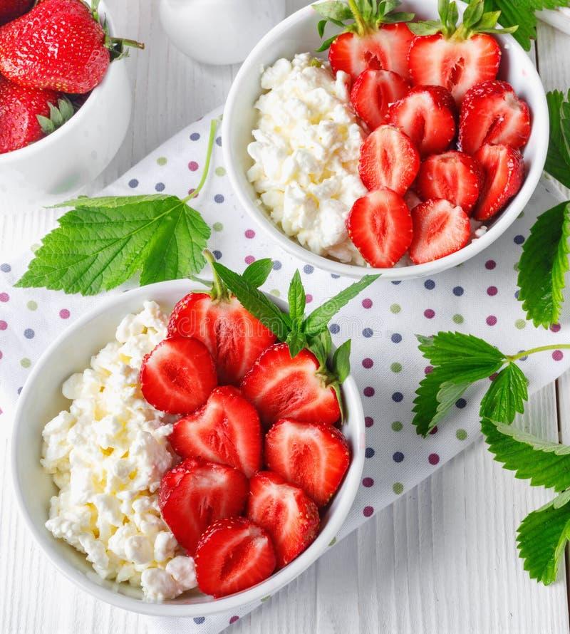 Vit bunke med nya r?da mogna jordgubbar och naturlig keso royaltyfria foton