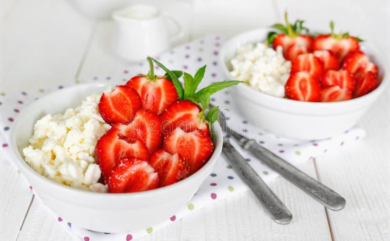 Vit bunke med nya r?da mogna jordgubbar och naturlig keso arkivbild