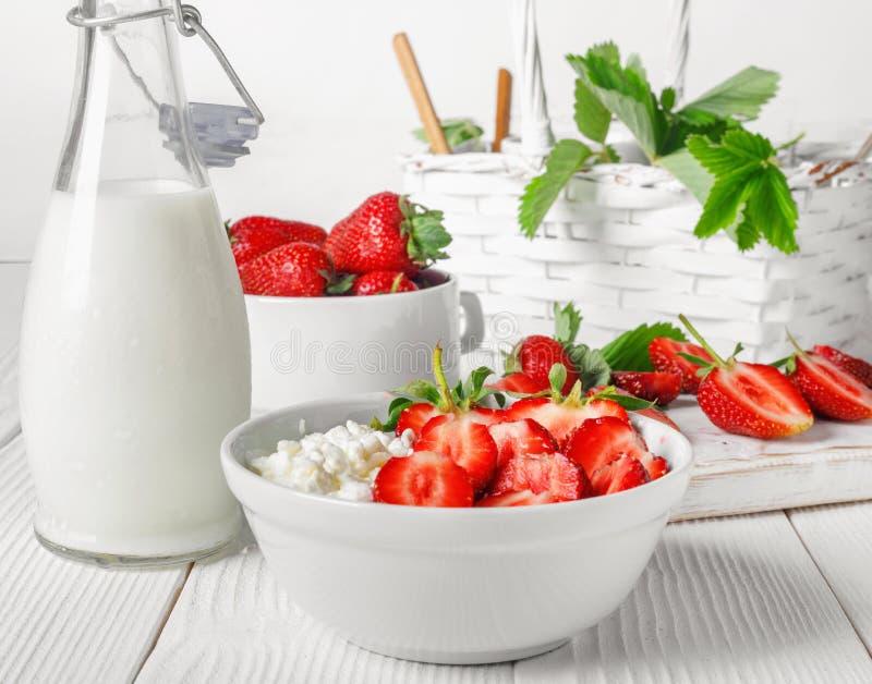 Vit bunke med nya r?da mogna jordgubbar och naturlig keso arkivbilder