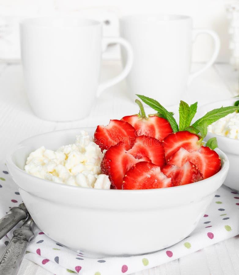 Vit bunke med nya r?da mogna jordgubbar och naturlig keso arkivfoto