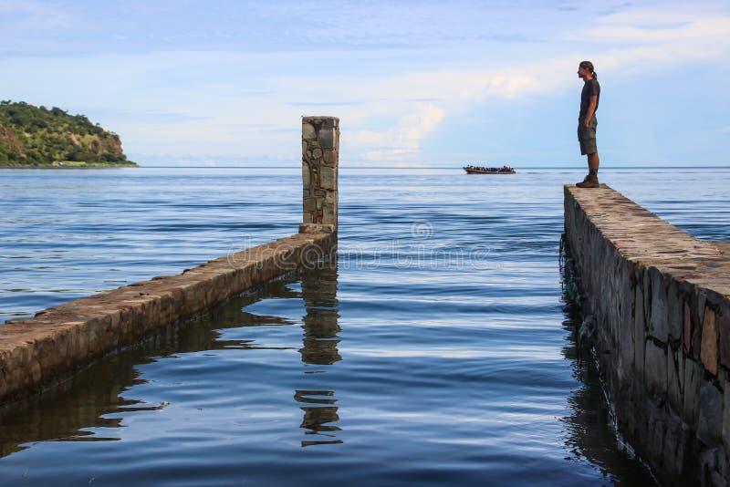 Vit Caucasian manlig handelsresande i sportswearen som står på en stenpir på den längsta sjön i världen Tanganyika royaltyfri fotografi