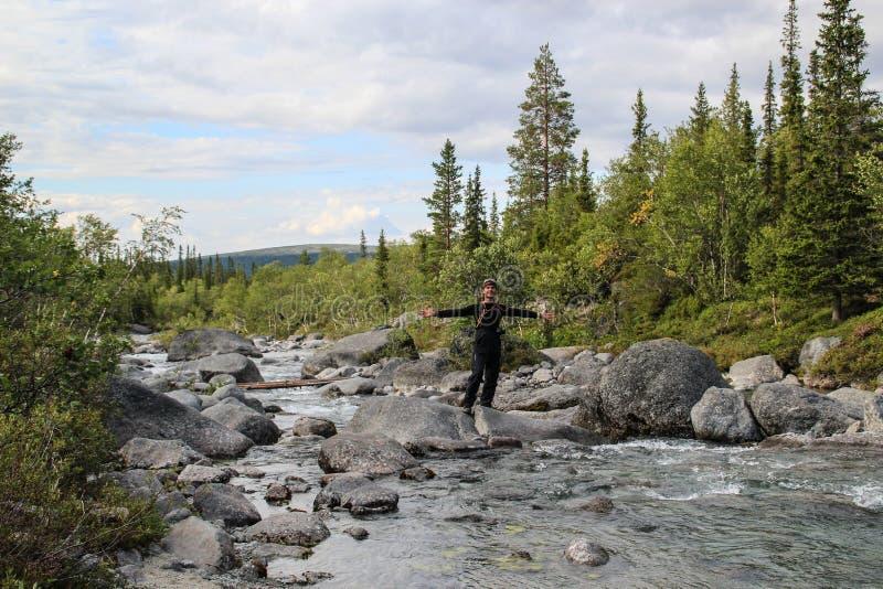 Vit Caucasian manlig turist i sportswearställningar i mitt av en bergflod med stenar arkivbild