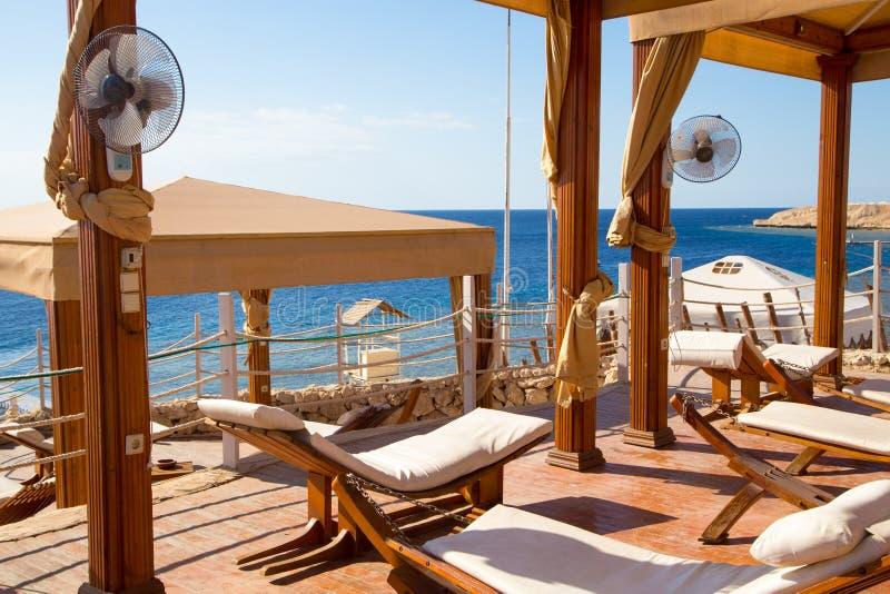 Vit chaise mot havet den härliga kusten, semestrar och kopplar av Vila zonen arkivfoto