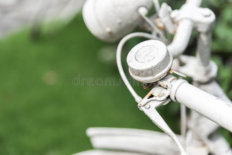 Vit cykel i tr?dg?rdbakgrund Tappning- och naturbegrepp St?ng sig upp och cykelhandtaget royaltyfri foto