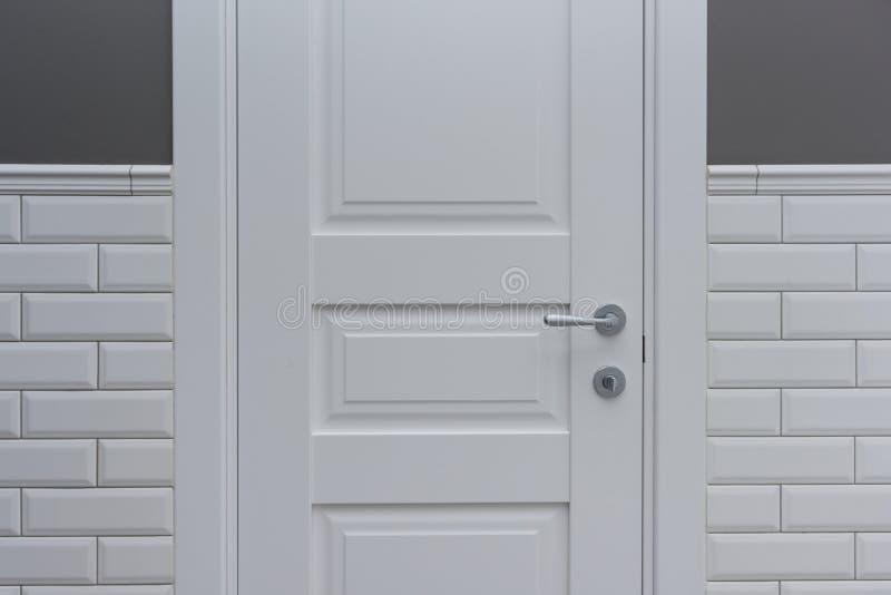 Vit dörr i badrumtoalettrummet Bakgrundsgrå färger målade väggen som täcktes med dekorativa keramiska tegelplattor med vit glansi arkivfoto