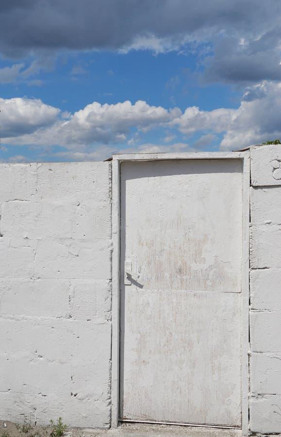 Vit dörr till molnen och himlen arkivbild