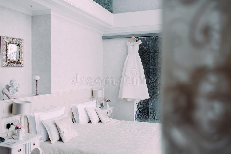 Vit elegant brud- klänning som hänger på en trähängare i lyxigt hotellrum i minimalist stil royaltyfria foton