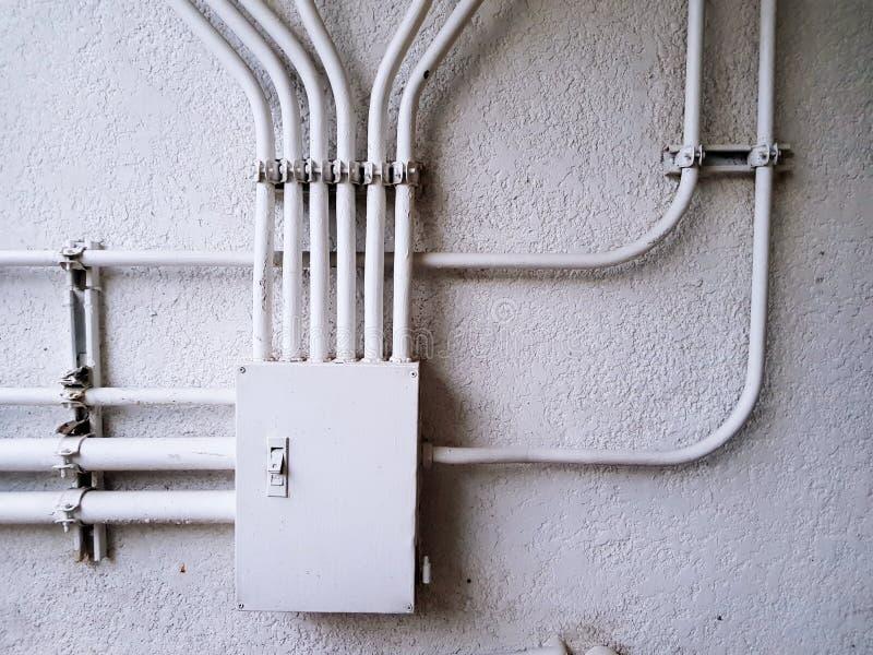 Vit elektrisk kontrollföreningspunktask för fördelningskraftledning på den vita betongväggen med kopieringsutrymme royaltyfri foto