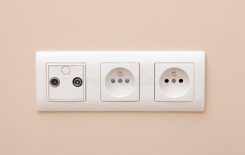 Vit elektrisk stickkontakt på väggen royaltyfri foto