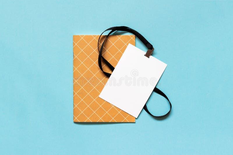 Vit emblemmodell och anteckningsbok för tomt papper på blå bakgrund Kopiera utrymme för text arkivbild