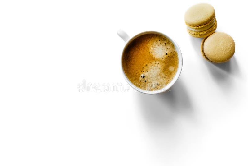 Vit espressokopp på vit bakgrund med makron royaltyfria bilder
