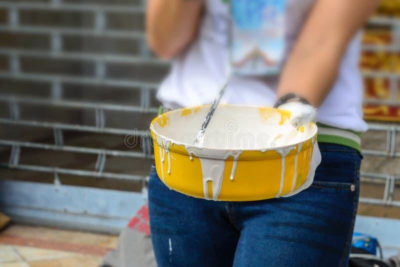 Vit färg i den gula hinken för målarfärgvägg med målarfärgrullen arkivfoton