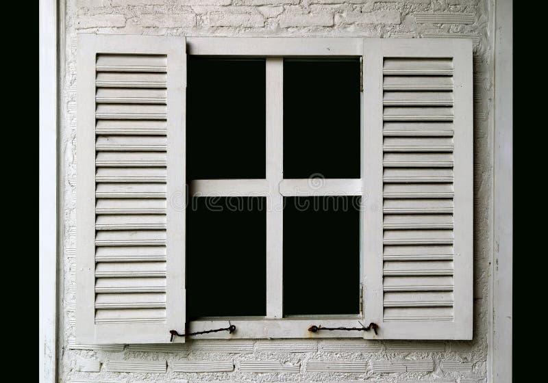 Vit färgade träfönstret på den vita målade tegelstenväggen arkivfoton
