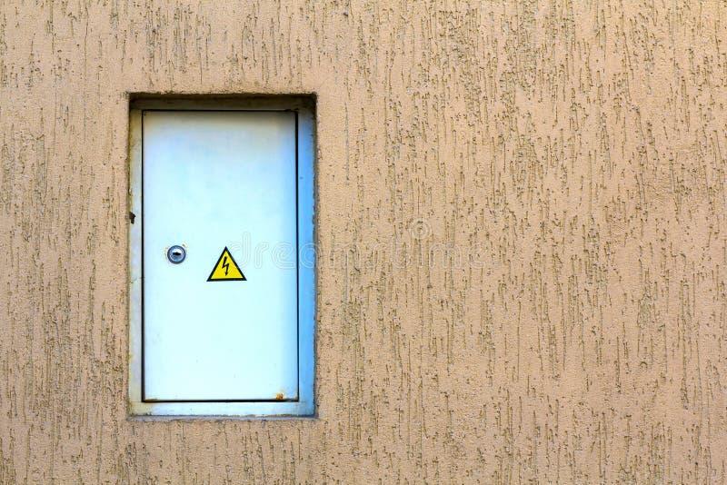 Vit försedd med gångjärn strömförsörjningask på väggen Elektrisk panel med arkivfoton