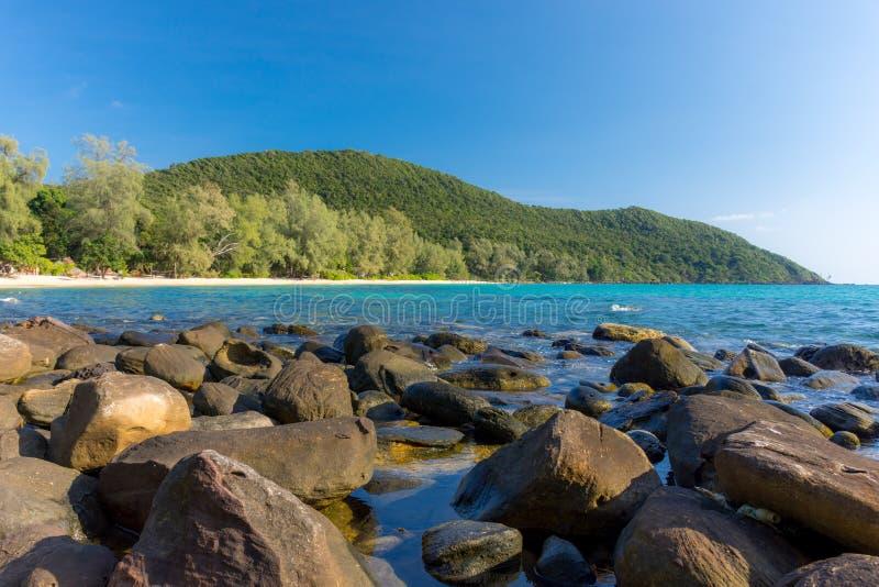 Vit fjärd för sandig strand med stora stenar i förgrund och skog royaltyfria foton