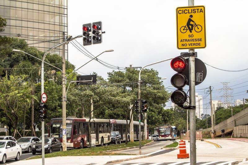 Vit fläck av cykel- och vitpilen som pekar en väg på asfaltbanan royaltyfri fotografi