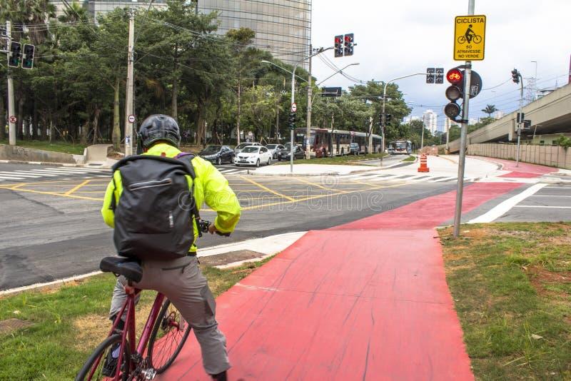 Vit fläck av cykel- och vitpilen som pekar en väg på asfaltbanan arkivbild