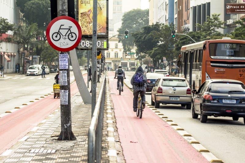 Vit fläck av cykel- och vitpilen som pekar en väg på asfaltbanan arkivfoto