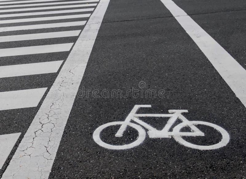 Vit fläck av cykel- och vitpilen som pekar en väg på asfaltbanan royaltyfri bild
