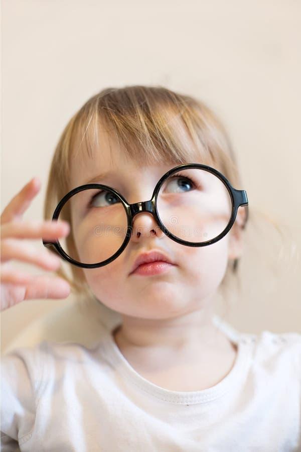 Vit flicka för roligt barn med stora runda svarta lärareexponeringsglas på hennes näsa royaltyfria foton