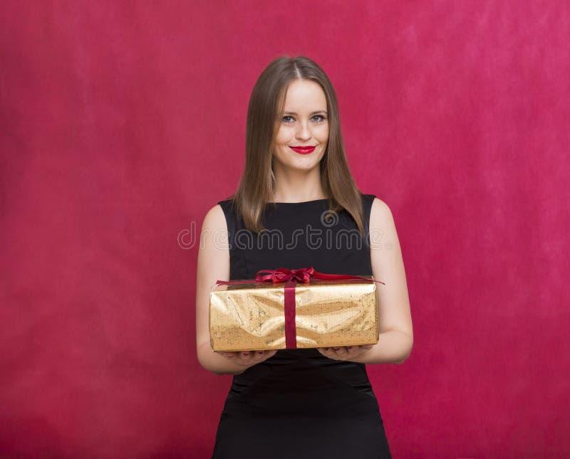 Vit flicka med en gåva i en guld- ask i hennes händer, en flicka i a royaltyfria foton