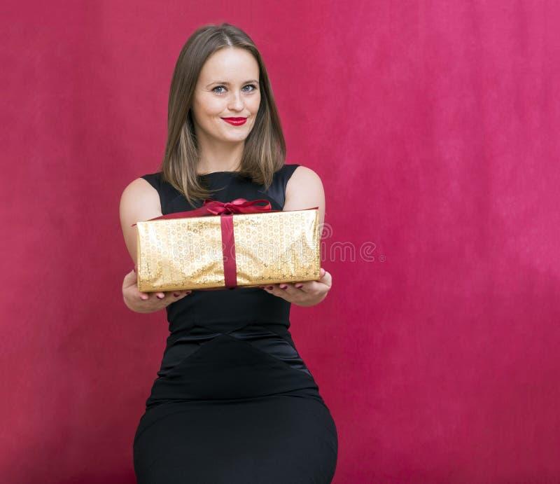 Vit flicka med en gåva i en guld- ask, en flicka i en svart klänning arkivfoton