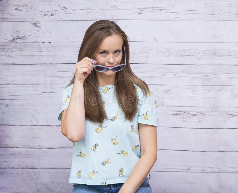 Vit flicka med långa håruppehälleexponeringsglas nära henne framsida, ung wom royaltyfri fotografi