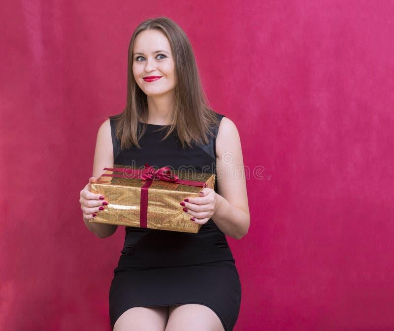 Vit flicka som rymmer en ask med en gåva i en guld- packe, gien arkivbild