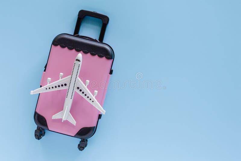 Vit flygplanmodell med den rosa resväskan på blå bakgrund royaltyfri foto