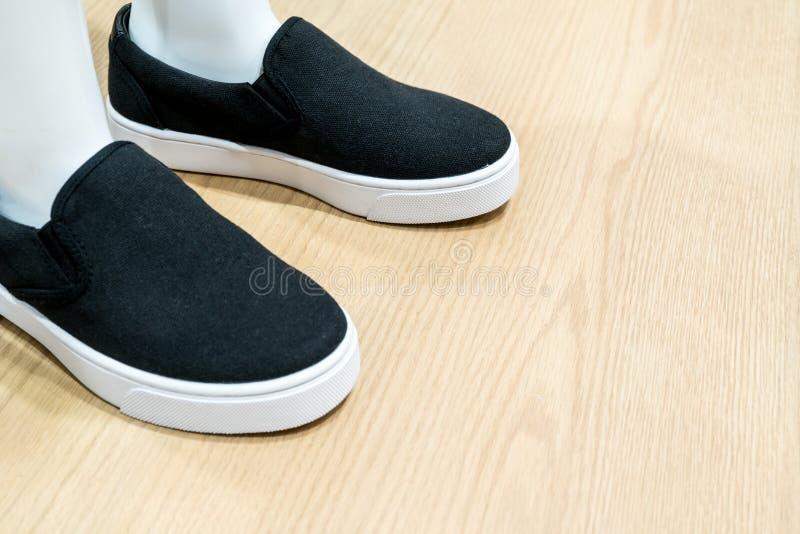 Vit fot för hudskyltdockamodell som bär den tillfälliga skon för svart kanfas royaltyfri bild