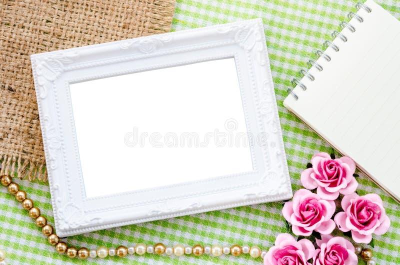Vit fotoram för tom tappning och öppen dagbok med rosa färgrosen på arkivfoto