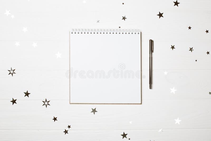 Vit fyrkantig formad anteckningsbok med pennan på pastellfärgad träbakgrund royaltyfri bild