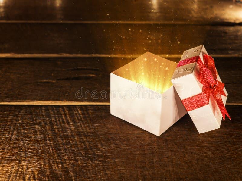 Vit gåvaask för öppen jul med strålen av magiskt ljus på träskrivbordet royaltyfri foto