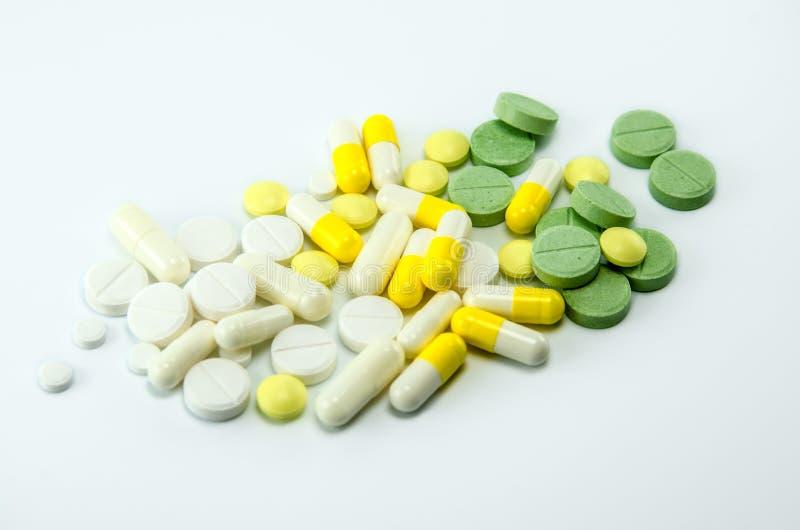 Vit-, guling- och gräsplanpreventivpillerar på en vit bakgrund arkivfoto