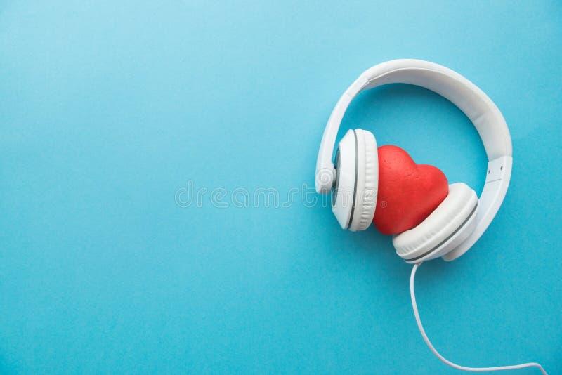 Vit hörlurar med det röda hjärtatecknet arkivfoto