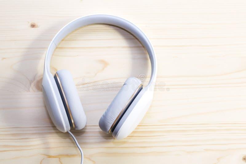 Vit hörlurar på träbakgrund arkivfoton