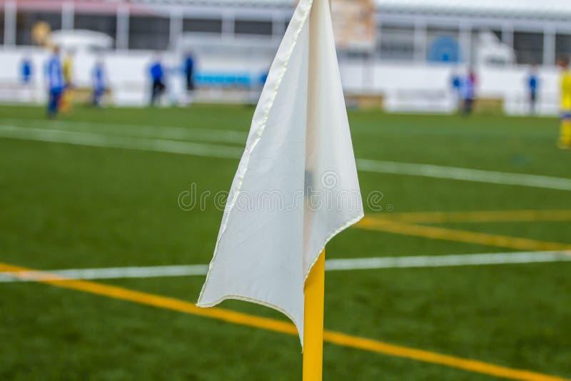 Vit hörnflagganärbild på bakgrunden av ett fotbollfält arkivfoto