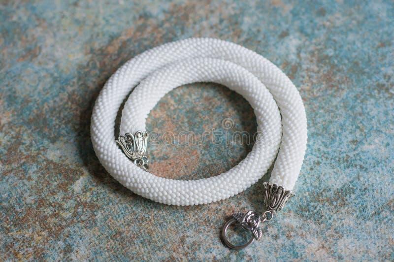 Vit halsband från pärlor på en textilbakgrund royaltyfria bilder