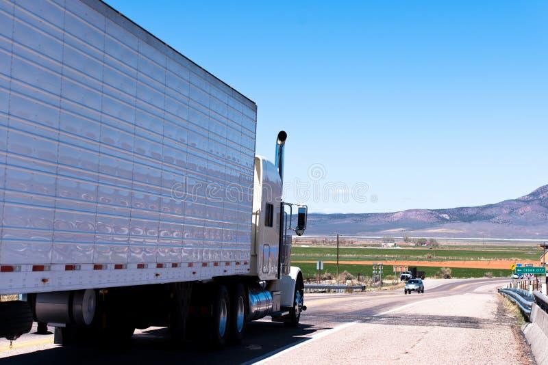 Vit halv lastbil och släp med reflexion på vägen royaltyfri foto