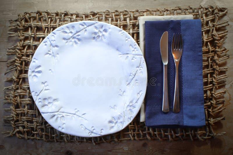 Vit handgjord platta med den blåa servetten på en lantlig vävd matt feriematställebakgrund arkivbilder